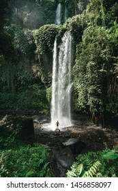 A man standing in front of big waterfall in the junle. Travel Indonesia. Hidden beauty of the island. Man standing at the bottom of the fall shows the scale of the waterfall