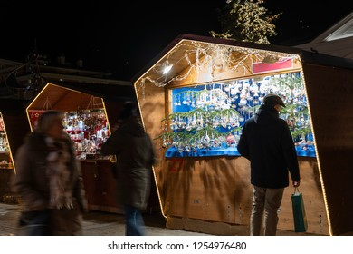 Man standing in front of a christmas market booth during night with a pouch in his hand in meran south tyrol italy, man shopping christmas gift, other blurred people passing by