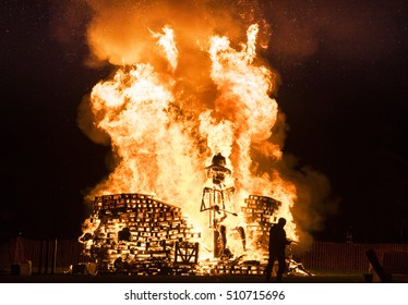 Man standing in front of a Guy Fawkes bonfire during the 5th of November at Lindifield bonfire night, West Sussex, England