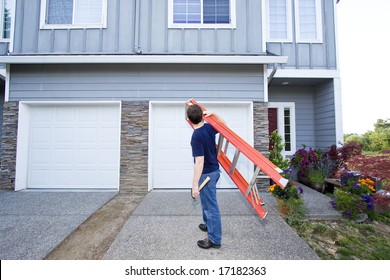 Man standing in front of house holding ladder and hammer. Horizontally framed photo.