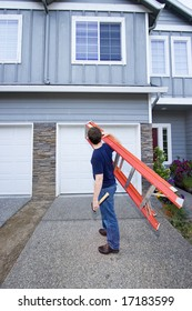 Man standing in front of house holding ladder and hammer. Vertically framed photo.