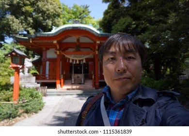 a man standing in front of kumano shrine at jiyugaoka in tokyo, japan