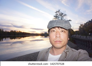 a man standing in front of magog river at promenade du lac des nations at rue de l'esplanade of sherbrooke town on the townships trail of eastern townships in quebec, canada