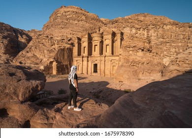 A man standing in front of the Monastery or Ad Deir in Petra ruin and ancient city in Jordan, UNESCO world heritage site, Asia