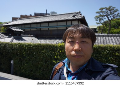 a man standing in front of old asakura house at daikanyama in tokyo, japan