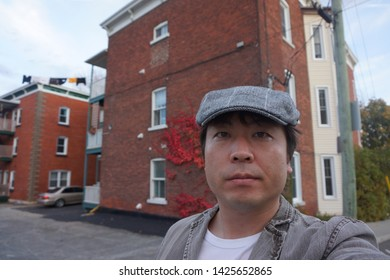 a man standing in front of residence houses at rue de la glaciere of sherbrooke town on the townships trail of eastern townships in quebec, canada