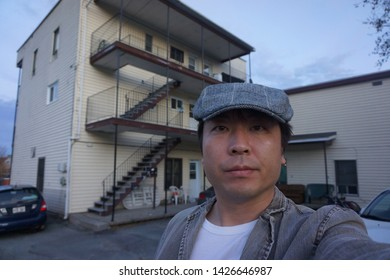 a man standing in front of residence houses at rue alexandre of sherbrooke town on the townships trail of eastern townships in quebec, canada