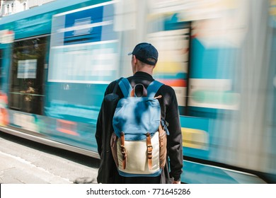 Man standing in front of road with tram. Male tourist in casual clothes with backpack is standing in front of road with tram is passing on sunny summer day. Move blur.