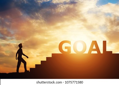 """Man standing in front of stairs with """"goal"""" writing on top. Career and achievement pursuit. Aspirations."""