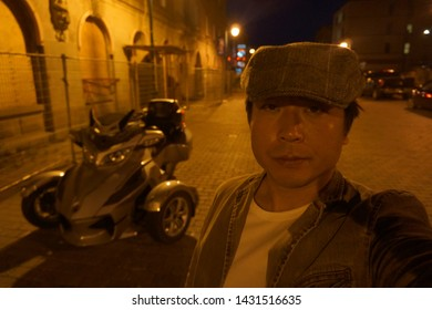 a man standing in front of unique 3-wheel motorbike at rue wellington south of sherbrooke town on the townships trail of eastern townships in quebec, canada in the night