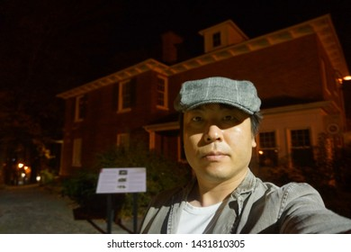 a man standing in front of uplands cultural and heritage center at rue uplands of sherbrooke town on the townships trail of eastern townships in quebec, canada in the night