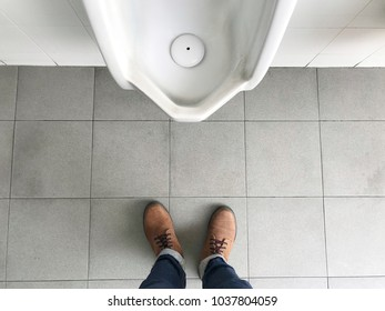 Man standing in front of urinal Top view of a man legs in front of urinal in men toilet