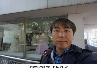 a man standing in front of wedding dress shop at hillside terrace area in daikanyama of tokyo, japan