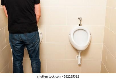 Man standing in front of a white pissoir in a public modern bathroom