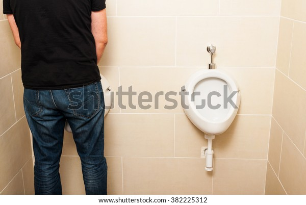 Man standing in front of a white pissoir in a public modern bathroom