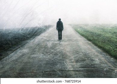 Man standing and gazing on rural foggy and misty grunge textured asphalt road.