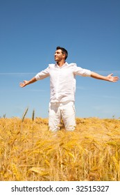 Man standing in a golden corn field with blue sky as symbol of insurance with arms wide outstretched