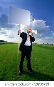 A man standing in a green field, holding a blank sign and shouting through a megaphone.