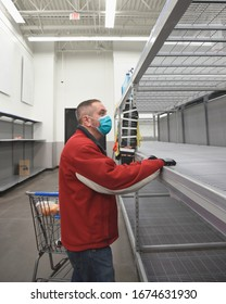 A man is standing in a grocery store wearing a virus mask looking at the empty rack shelf for a corona virus pandemic concept.