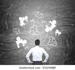 A man standing with hands on hips, a blackboard with parts of a puzzle drawn in front of him. Back view. Concept of getting a full picture.