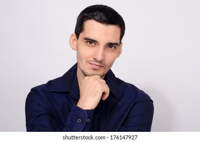 Man standing with his arm at the chin smiling. Portrait of a young business man wearing a dark blue shirt.