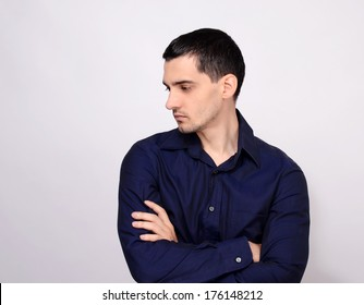 Man standing with his arms crossed looking down over the shoulder to the side from profile. Portrait of a young business man wearing a dark blue shirt.