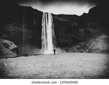 Man standing with his arms outstretched in front of a waterfall in Iceland