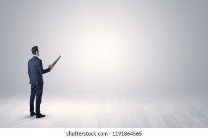 Man standing with his back in an empty room with object in his hand