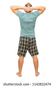 A man is standing with his back in his pajamas with his hands behind his head on a white background. Isolated.
