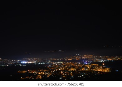 man standing with his car on a hill overlooking a big city at night in the moonlight with the night lights of the city on a fog background in the sky and a stunning sensation