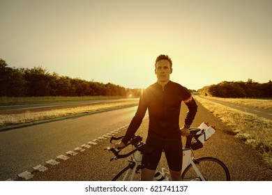 Man standing and holding a bicycle on the empty road in the evening.