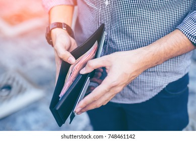 Man standing holding black wallet full of money