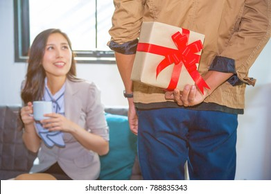 Man standing and holding valentine's gift box behind his back for surprise his lovely girlfriend.