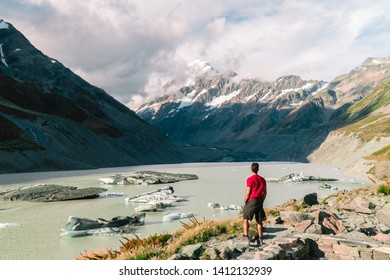 Man standing at ice Glacier lake at the top of Mount Cook from the Hooker trail tramping trek. Dramatic. Snow capped Mountain background. Grey red moody. Shot in Pukaki South Island, New Zealand.