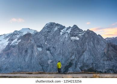 Man standing in Italian dolomites under a Marmolada.