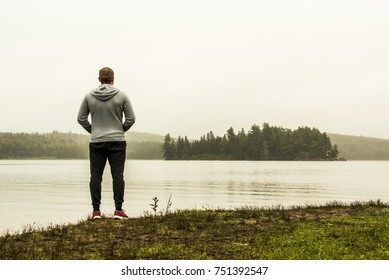 Man standing at lake of two rivers algonquin national park watching ducks Ontario Canada on a grey morning atmosphere