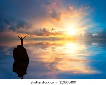 A man standing at lonely rock in the ocean with open arms set against a beautiful sunrise, clouds reflection in water