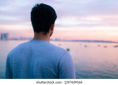 Man standing and looking at beautiful landscape of Chitgar lake and Tehran.