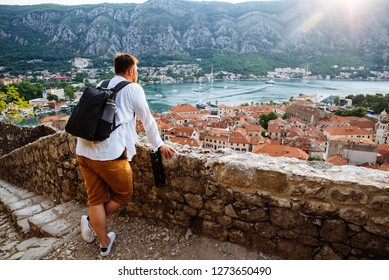 man standing and looking on sunset over kotor city in montenegro
