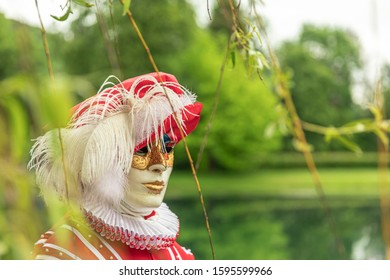 A man standing in mask and red masquerade costume agains the pond background