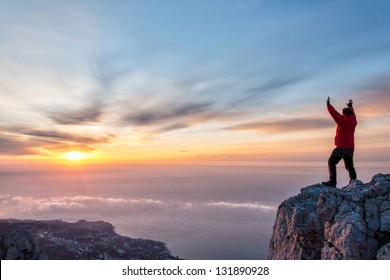 A man standing at mountain top with open arms set against a beautiful sunrise, feeling freedom