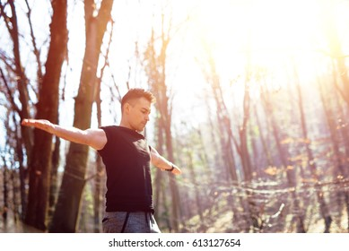 Man standing in nature with arms outstretched