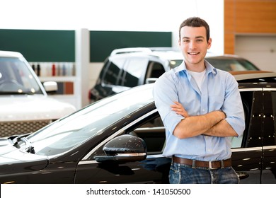 man standing near a car with his arms crossed, car showroom