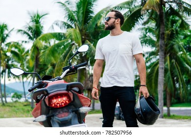 Man standing near his motorbike with helmet on palm background