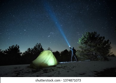 man standing near illuminated tent and pointing blue flashlight to starry sky in winter Nebrodi Park, Sicily