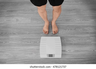 Man standing near weight scales on wooden floor