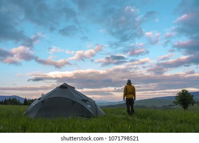 man standing next to a tent pitced on a meadow, looking at a clouds during sunset