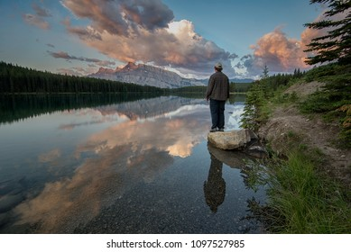 Man standing next to a tranquil lake with an amazing mountain reflection.