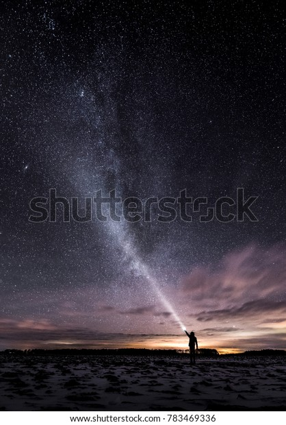 A man standing at night with a flashlight and lighting to the stars