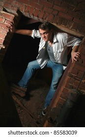A man standing in an old brick opening